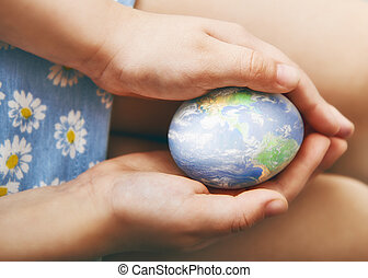 hands holding an Easter egg - childrens hands holding an...