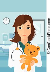Pediatrician holding teddy bear - A pediatrician holding a...