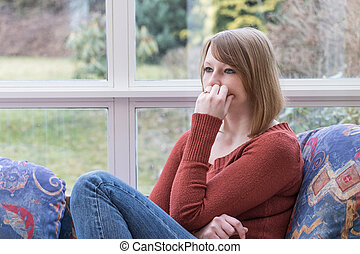 Pensive young woman dressed in a brown sweater is sitting on...