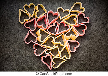 Red and yellow heart shaped pasta in shape of heart, top view, food background