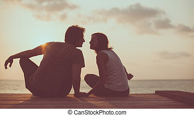 Flirting couple on the tropical sunset background. -...