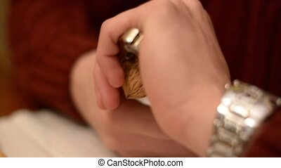 Hands of young man cracking nut with nutcracker - Close up...