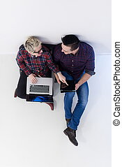 top view of couple working on laptop computer at startup...