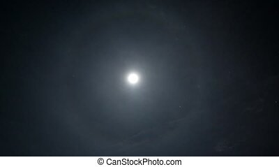 Full Moon on night sky with clouds and halo