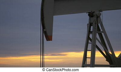Oil pump with sunrise in the background - Working oil pump...