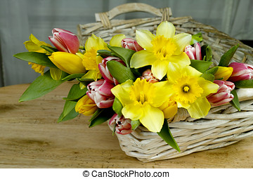 Multicolored bouquet spring flowers with wicker basket on...