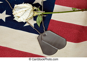 Tribute - Military dog tags with dried rose on flag.
