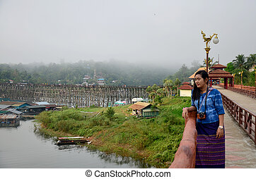 Thai woman travel and portrait on Saphan Mon wooden bridge...