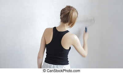 Beautiful woman painting wall with white paint