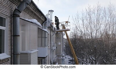 Man removing icicles from eaves