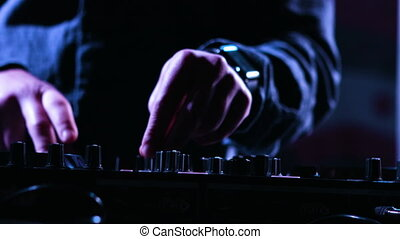 Close-up footage of a male DJs hands mixing music at a party...