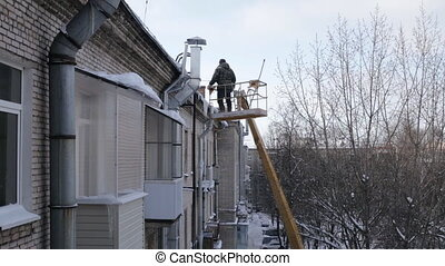 Strong man removing ice dams from roof