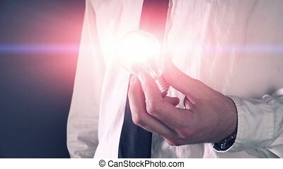 Business idea and vision, businessman holding shining light...