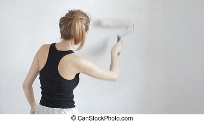 Woman painting wall in white with a paint roller