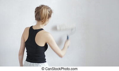 Young woman painting wall - Beautiful young woman painting...
