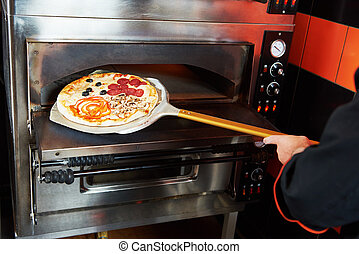 chef baker cook taking out pizza from the oven