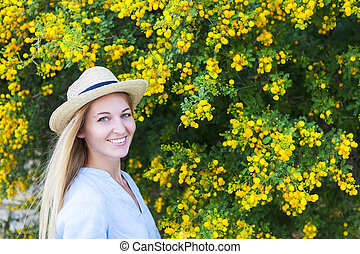 Portrait of a beautiful young woman in the hat with mimosa flowers