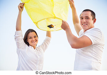 Young couple start a Chinese sky lantern in the dusk near...