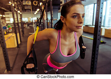 Woman in gym - Attractive young woman training with trx...