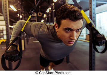 Man in gym - Handsome young muscled man training with trx...