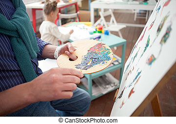Skillful old artist and his small grandchild - Close up of...