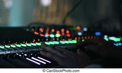 Close-up picture of male hands put on a sound control desk. Audio engineer operates his instrument, recording equipment, during a night show at concert hall.
