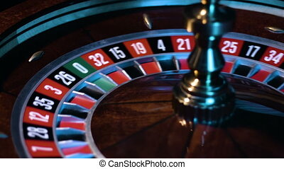 Russian roulette wheel is spinning with the small white ball is going around at the game table at casino.