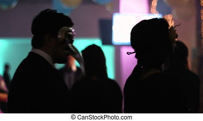 Two people within audience are dancing back to camera, man and woman moving to the music with masquerade masks on their faces at the special styled event.