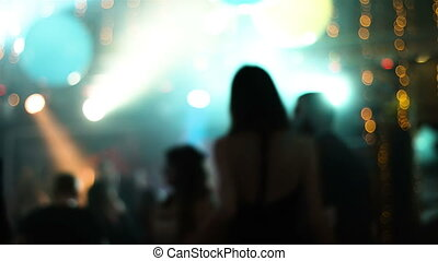 Blurred footage with young attractive people dancing in a nightclub. Girl dancing back to camera.