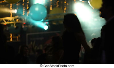 Silhouette of a long haired woman is dancing in a nightclub at a party, full of happiness and enthusiastic girl is spinning and whirling on a dancefloor.