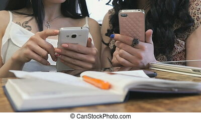 Two girls using smart phone in cafe Closeup - Two business...