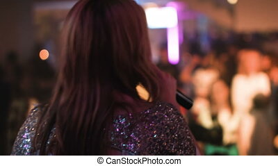 Female vocalist standing back to camera singing a song at a nightclub,audience is dancing under the stage.