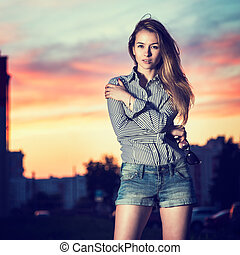 Portrait of Beautiful Girl in Evening City Embracing Herself...