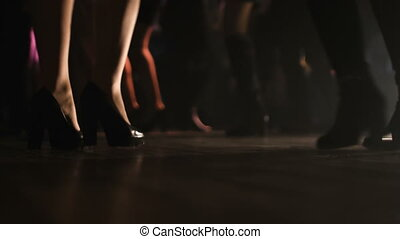 Close-up picture of two pairs of female legs on heels dancing on a dancefloor.