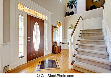 Nice entryway to home with carpeted staircase, and white...