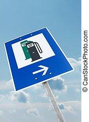 Fuel station sign against blue sky