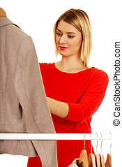 Woman deciding what to put on - Young woman deciding what to...
