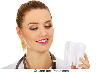 Female dentist holding a tooth model. - Happy female dentist...