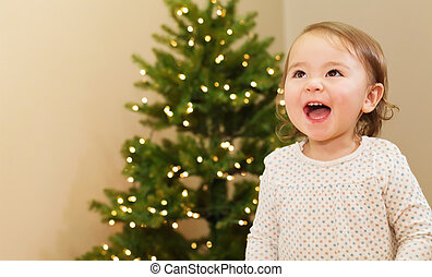 Cheerful girl smiling in front of the Christmas tree