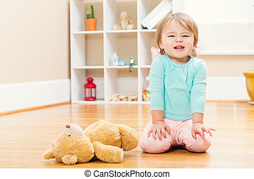 Happy toddler girl playing with her teddy bear - Happy...