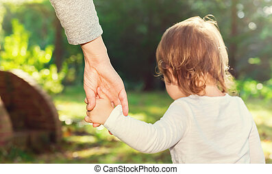 Toddler girl holding her parents hand outside