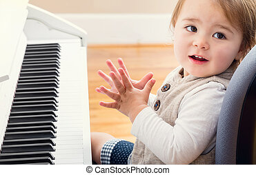 Happy toddler girl playing piano - Happy smiling toddler...