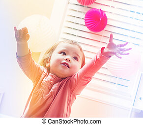 Happy toddler girl playing with toys