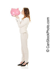 Business woman kissing a piggybank - Happy business woman...