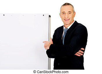 Male executive pointing on flip chart - Mature businessman...