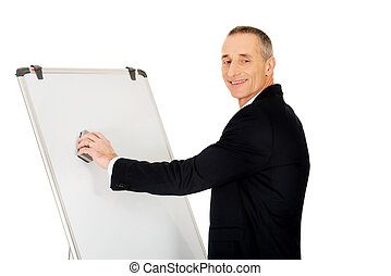 Male executive cleaning a flip chart - Mature businessman...