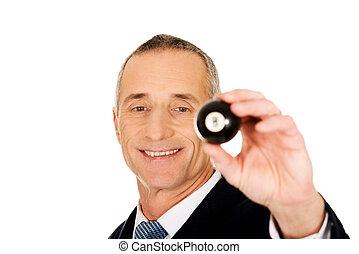 Businessman holding black billiard ball