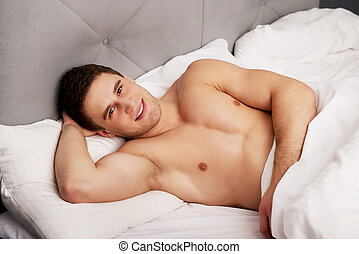 Handsome young man lying in bed.
