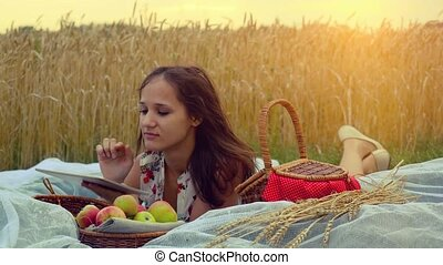 Young beautiful smiling woman with tablet pc on picnic in...