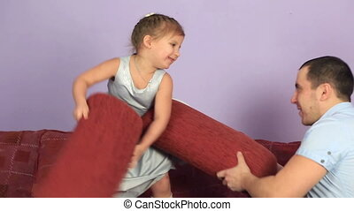 Cheerful father and daughter fighting pillows on couch. -...